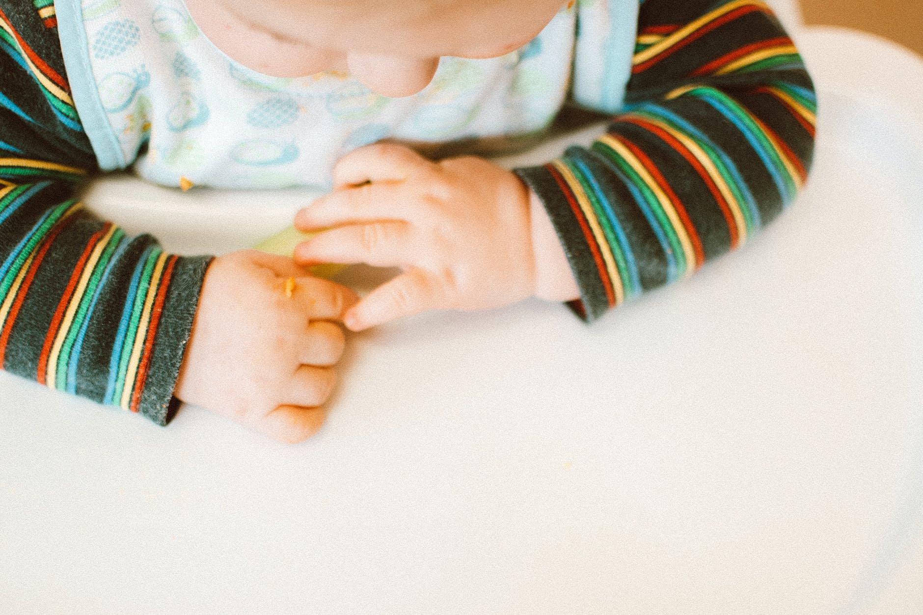photo of kid wearing colorful long sleeves sitting on high chair