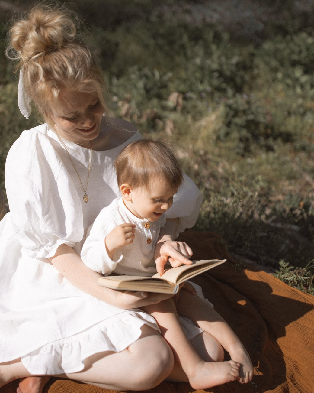 photo of woman and baby reading a book