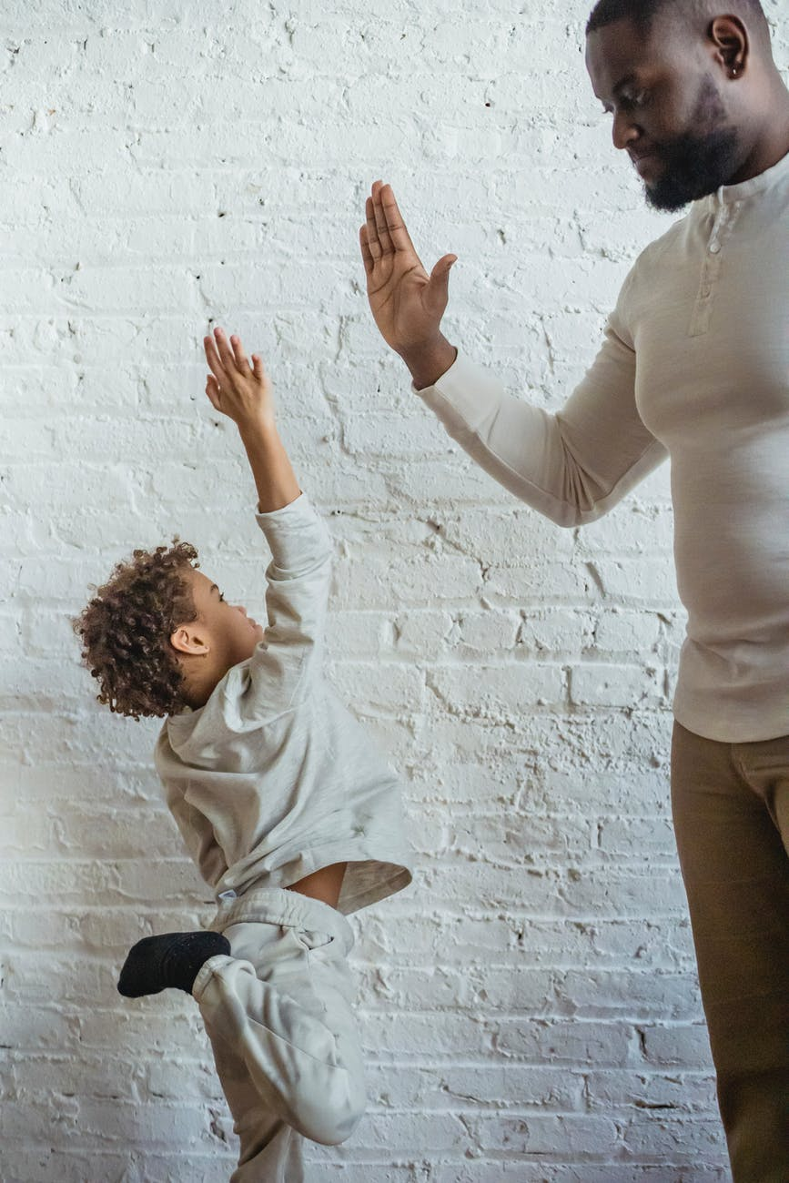 black father and son doing high five